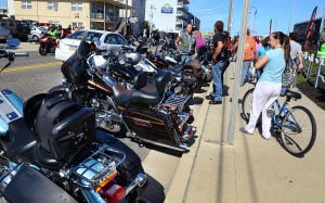 ROAR TO THE SHORE: People look at motocycles parked on Ocean Avenue in front of the Convention Center. Saturday September 7 2013 Tens of thousands of motorcycles gather in Wildwood this weekend for the annual Roar to the Shore. (The Press of Atlantic City / Ben Fogletto) - Ben Fogletto