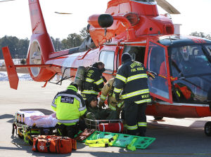 """AIRPORT DISASTER DRILL: Firefighters remove an """"injured"""" pilot Jared Mandella, Major, of the 177th Fighter Wing, from a Coast Guard helicopter, Tuesday Feb. 11, 2014, during joint agencies mishap drill at the William J. Hughes Technical Center in Egg Harbor Township. (Staff Photo by Michael Ein/The Press of Atlantic City) - Michael Ein"""