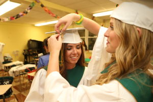 OLMA Graduation: Olivia Kiefer, 17 of Greenwich, right helps Jacqueline Battaglia, 18, left of Cape May Court House with her cap before their Graduation at Our Lady of Mercy Academy Tuesday May 27, 2014. - Edward Lea