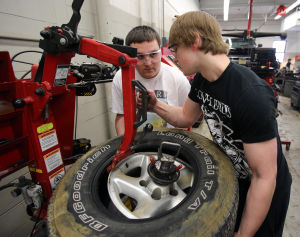 Votech Training: Automotive technology students Jack Dennison of Cape May, (left) and Steve Nessler of Dennis Township, mount tires on rims in class. - Dale Gerhard