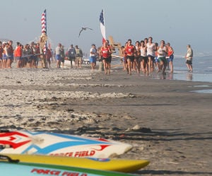County Lifeguards: Competitors in the rescue board race, run to get their boards at the start of the race. The Cape May County Lifeguard Championships were held on Rambler Road Beach in Wildwood Crest, with nine county beach patrols participating. Friday July 5, 2013. (Dale Gerhard Photo/Press of Atlantic City) - Dale Gerhard