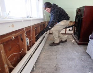 Restoration 2: Adam Prettyman, of North Cape May and Colonial Carpet Cleaning and Restoration, vacuums the walls behind heater units at a home in Sea Isle City.  - Dale Gerhard