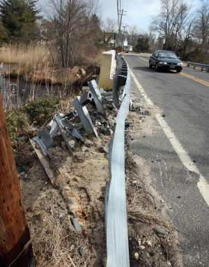 : A view of the dam side of the bridge with damaged guardrail at Willow Grove Lake on the Cumberland side. Cumberland and Salem counties have agreed on a $7.2 million plan to rebuild the Willow Grove Lake dam and spillways. The dam and spillways have been temporarily shored up since August 2011, when heavy rains and floodwaters threatened to wash out the area and flood North Vineland. Wednesday Feb 20, 2013. (Dale Gerhard/The Press of Atlantic City)  - Dale Gerhard