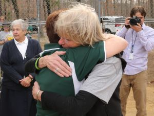 OLMA Softball: Melissa Connor, head coach of Our Lady of Marcy Academy softball team gives a hug to Geri Patrick of Georgia mother of former softball coach Jamie Cook who died suddenly over the winter at a young age Tuesday, April 8, 2014. - Edward Lea