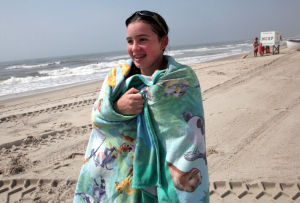 Cold Water: Michaela Sykes, of Philadelphia, Pa., warms up in a towel after leaving the chilly water off the beach near Gladstone Avenue, in Margate, NJ, Wednesday July 10, 2013. Water temperatures for the ocean have been colder than usual this summer, a bummer for beachgoers. - Photo by Vernon Ogrodnek