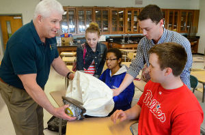 CAR CRASH PHYSICS: Wayne Shelton of Upper township, retired State Police, shows a deployed airbag to students, (l-r) Becca Adamo, 18, Argiea Spencer, 17, Matt Mazzone, 17 and James Townley, 17, all of Mays Landing. Tuesday April 9 2013 South Jersey Traffic Alliance conducts a program on the physics of driving and crashes as part of safe driving program in a physics class at Oakcrest High School in Mays Landing. (The Press of Atlantic City / Ben Fogletto)  - Ben Fogletto