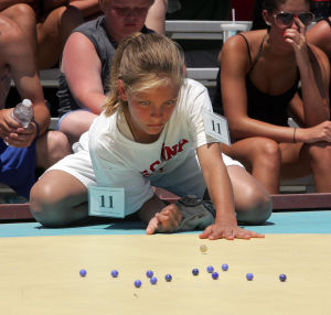 : Girls champion Emily Cavacini 11, of Allegheny Pa,. shoots during the finals of the 90th annual National Marbles Tournament held on the beach at Ringer Stadium in Wildwood. Thursday June 20, 2013. (Dale Gerhard/The Press of Atlantic City)  - Dale Gerhard