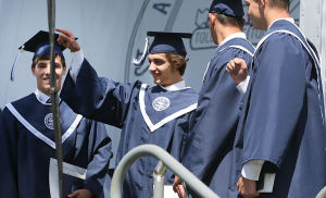 ST. AUGUSTINE GRADUATION: Graduate Ryan Piscitelli of Voorhees (2nd from left) points to fellow students after receiving his diploma with members of the baseball team who had to leave commencement early to play a school game. The event was held outside on campus. Sunday May 18 2014 St. Augustine Prep Graduation. (The Press of Atlantic City / Ben Fogletto) - Ben Fogletto
