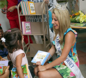 Miss NJ In Margate: Cara McCollum, Miss New Jersey, originally from Forrest City, Arkansas, hands out books to children at the Margate Library, in Margate, Wednesday July 10, 2013. - Photo by Vernon Ogrodnek
