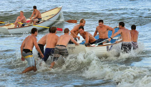 Bill Kuhn Brigantine Races: Ventnor's Vince Dipeatino and Drew Remy are pushed out by teammates after a crew switch during the Surf Boat Relays. Monday July 8 2013 Chief Bill Kuhn Brigantine Beach Patrol Invitational Races in Brigantine. (The Press of Atlantic City / Ben Fogletto) - Ben Fogletto
