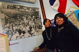 Mac Exhibit: Bernadette Matthews of Cape May, left, and Wanda Evelyn of Rio Grande talk Friday next to a photo of black troops waiting to watch a USO show during WWII. The Mid-Atlantic Center for the Arts will open an African-American themed exhibit on Martin Luther King Day at the Carriage House at the Emlen Physick Estate.  - Photo by Ben Fogletto