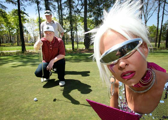The At The Shore visitor from the future (Anjelia Pelay) watches Bob Lively, front, and Tom Macdonald, both of Medford, Conn., play a round of golf at  Blue Heron Pines Golf Club in Egg Harbor City.