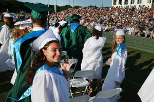 Mainland Reg Graduation: Graduate Vanessa Francesco of Somers Point (left) waves during commencement. Tuesday June 24 2014 Mainland Regional Graduation. (The Press of Atlantic City / Ben Fogletto) - Ben Fogletto