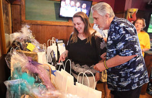 Mullica Teacher Benefit: Mullica kindergarten teacher Kelly Mascio and her father, Fran McIntyre of Mays Landing look at items gathered for the silent auction. Sunday April 13 2014 Fund raiser at JD's Pub in Smithville to help Mullica kindergarten teacher Kelly Mascio pay her bills while suspended without pay. (The Press of Atlantic City / Ben Fogletto) - Ben Fogletto