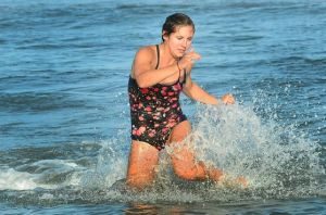Upper Twp. Repeats As Team Champ: Katie Collins comes out of the water while competing for the Wildwood Beach Patrol in the paddleboard relay race Monday night in Upper Township. Wildwood won that race.