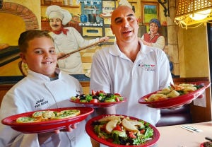 ATS-La Pizzatega Restaurant: Owner Glen McCauley and his son, Joey, 10, hold signature dishes. Friday September 27 2013 La Pizzatega in Linwood. (The Press of Atlantic City / Ben Fogletto) - Photo by Ben Fogletto