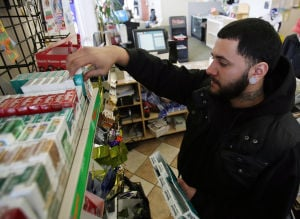Cigarettes: Angel Perez of Vineland stocks cigarettes at Molina's News Stand at the bus station on Landis Ave in Vineland. Perez said the sale of cigarettes may increase in the store when CVS, one block away, stops selling them completely. CVS will be eliminating the sale of cigarettes in their stores over the next few months. - Dale Gerhard
