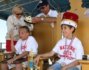 : Girls Champion Emily Cavacini 11 of Allegheny Pa. (left) and boys champion Cooper Fisher 12, of Middletown Valley, Md. are crowned king and queen of the tournament by Beri Fox (back left) President of the tournament and Rick Mawhinney, Tournament Director. The finals of the 90th annual National Marbles Tournament were held on the beach at Ringer Stadium in Wildwood. Thursday June 20, 2013. (Dale Gerhard/The Press of Atlantic City)  - Dale Gerhard