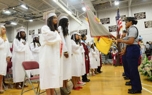 PLEASANTVILLE GRADUATION: Class stands for flag salute. Tuesday June 18 2013 Pleasantville High School Graduation, held inside the gym due to in-clemate weather. (The Press of Atlantic City / Ben Fogletto)  - Photo by Ben Fogletto