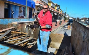 Downtowns In The Velocity Zone: Richard Neer of Nashville Tenn., with Restore One of Nashville, carries damaged wood to a dumpster from the Heritage Surf Shop on Ventnor Avenue. Monday February 18 2013 Margate's downtown is right in the middle of a bowl-shaped depression that is part of the proposed velocity zone on the new FEMA flood maps - one of the few in the area to do so. (The Press of Atlantic City / Ben Fogletto)  - Ben Fogletto