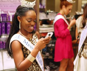 Miss A Social Media: Miss Virgin Islands Ashley Massiah uses her cellphone to tweet at the new Miss America store at the Piers At Caesars on Thursday. - Edward Lea