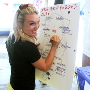 Petrosh: Current Miss New Jersey Lindsey Petrosh of Egg Harbor City, signs the map listing all the contestants. Contestants for this year's Miss New Jersey Pageanton theOcean City Music Pier arrived in town and began rehearsal for pageant which begins on Thursday. Tuesday June 11, 2013. (Dale Gerhard/The Press of Atlantic City)  - Dale Gerhard