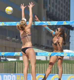 AVP BEACH VOLLEYBALL: Olaya Pazo, of Miami, FL, right, spikes against the team of Emily Day, of Torrance, CA, during a qualifier match, Friday Sept. 6, 2013, at the AVP Beach Volleyball tournament in Atlantic City. (Staff Photo by Michael Ein/The Press of Atlantic City) - Michael Ein