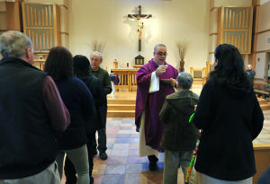 Ash Wednesday: Euharistic Minister Gabe Ingegeri, of Galloway Township , left, and Rev. John Picinic, right, deliver communion on Ash Wednesday to parishioners at Our Lady of Perpetual Help parish church in Galloway Township, on Wednesday, Feb. 13. (Staff Photo by Michael Ein)  - Michael Ein