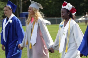 Oakcrest Graduation: From left; Shawn Taylor, 18, Amber Anthony, 18, and Christl Stringer, 18, hold hands as they march in the graduation ceremony, Friday June 20, 2014, at Oakcrest High School in Mays Landing. - Michael Ein