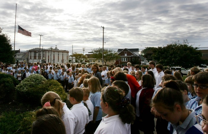 Students bow their heads during prayer Friday at a ceremony in remembrance of 9/11 held outside Wildwood Catholic High School in North Wildwood.