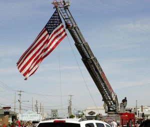 : North Wildwood Firemen hoist a large flag during the ceremony. Memorial Day services held at Veterans Memorial on Spruce and New Jersey Avenues in North Wildwood. Monday May 27, 2013. (Dale Gerhard/The Press of Atlantic City)  - Dale Gerhard