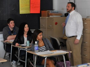 Oakcrest In The Schools: Social studies teacher Rick Schwartz, right, gives a lesson on the Beatles' Revolver album Thursday at Oakcrest High School as students Ted Price, 17, left, Kelsey Botbyl, 16, and Allison Pham, 16, all of Mays Landing, listen.  - Photo by Michael Ein