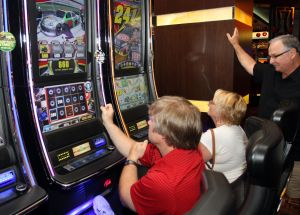 : Glenn Souchuck of Frackville, Pa., (left) and Louann Green of Sicklerville, play the new NASCAR slots at Golden Nugget. Ron Green, Louann's husband (right) looks on. A new type of NASCAR-themed slot machine is making its Atlantic City debut at the Golden Nugget. Packed with new features, it represents the next generation of slot machine technology and puts slot players in the virtual driver's seat in the race for prizes. Friday June 7, 2013. (Dale Gerhard/The Press of Atlantic City)  - Dale Gerhard