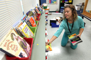 First Day Of School: Second-grade teacher Mary Hodgens, of Linwood, puts away books in her classroom in preparation for the first day of school at the Galloway Community Charter School, in Galloway, on Thursday. - Photo by Vernon Ogrodnek
