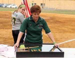 OLMA Softball Game Vs. Pleasantville: Melissa Connor, head coach of Our Lady of Marcy Academy softball team percent a jersey ball and bat to Geri Patrick of Georgia mother of former softball coach Jamie Cook who died suddenly over the winter at a young age Tuesday, April 8, 2014. - Edward Lea