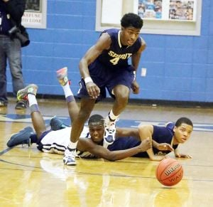 Holy Spirit At Atlantic City Boys Basketball: Holy Spirit's Leon Daniels #4 middle chase down a loose ball against Atlantic City's Dennis White #3, left background and his teammate Tyler Jones #24, right background during basketball game at Atlantic City High School Wednesday, Feb 19, 2014. - Photo by Edward Lea