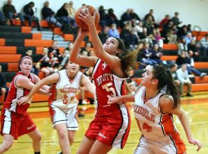 O.C. Photo: Ocean City's Natalie Landi, left, grabs a rebound over Middle Township's Olivia Schwartz, right, at Middle Township High School on Tuesday.  - Edward Lea