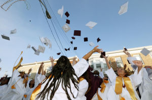 Wildwood High School Graduation: Wildwood High School graduates toss their caps into the air on Pacific Avenue in front of the school after the graduation ceremony. Wildwood High School held their 108th commencement ceremony in the school's Dr. Stanley M. Hornstine Auditorium Tuesday June 17, 2014. (Dale Gerhard/Press of Atlantic City) - Dale Gerhard