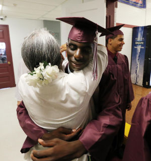 Wildwood High School Graduation: Wildwood High School senior Devonte Oglesby receives a hug from teacher Betty Harshaw. Wildwood High School held their 108th commencement ceremony in the school's Dr. Stanley M. Hornstine Auditorium Tuesday June 17, 2014. (Dale Gerhard/Press of Atlantic City) - Dale Gerhard