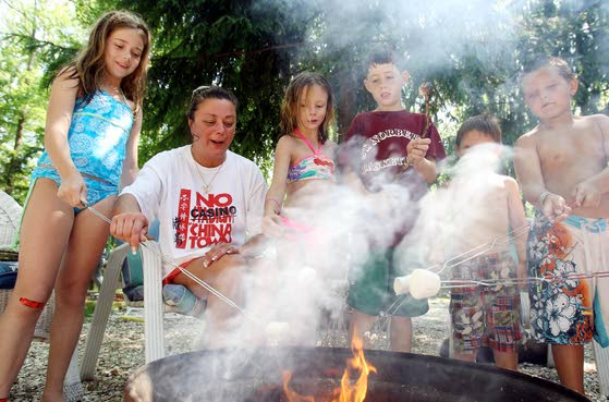 Donna Hural, of Cherry Hill, center, gathers around the campfire with her daughter, Morgan, family friends Elizabeth and Johnny Foster, and her nephews, Joseph and Vincent Fabrizio, at the Acorn Camping Resort on Route 47 in the Green Creek section of Middle Township.