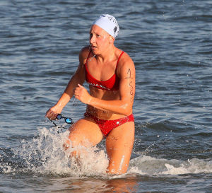 : Sea Girt's Annie Skimmons, exits the water at the end of the swim to win the race. Cape May Point Women's Lifeguard Challenge, a short run-paddleboard-swim triathlon for women lifeguards Monday July 29, 2013. (Dale Gerhard Photo/Press of Atlantic City) - Dale Gerhard