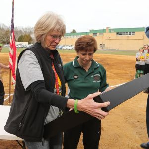 OLMA Softball: Melissa Connor, right, head coach of the Our Lady of Marcy Academy softball team, presents a jersey, ball and bat to Geri Patrick, left, of Georgia on Tuesdayin Newfield. Patrick is the mother of former softball coach Jamie Cook who died suddenly over the winter. - Edward Lea