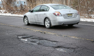 Pothole Map: Cars travel through potholes on Millville Ave between Harley and Baker Aves in Mays Landing. Tuesday March 4 2014 (The Press of Atlantic City / Ben Fogletto) - Ben Fogletto
