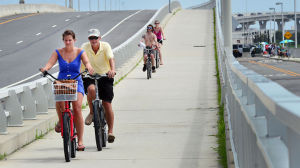 BIKING ROUTE 52: Gina Hall (left) and her father, Pete Hall of Ocean City (center) use the bike path on the Route 52 Causeway Bridge between Somers Point and Ocean City. (The Press of Atlantic City / Ben Fogletto) - Ben Fogletto