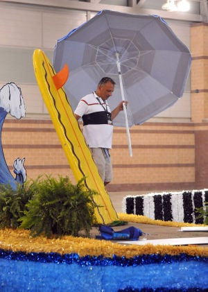 MISS AMERICA PARADE ADVANCE: Todd Marcocci, of West Chester, installs a beach umbrella onto the Catalina Swimwear parade float, Friday Sept. 13, 2013, at the Atlantic City Convention Center ahead of Saturday's Miss America Show Us Your Shoes Parade. (Staff Photo by Michael Ein/The Press of Atlantic City) - Photo by Michael Ein