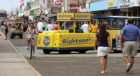 A tram car makes a sweeping turn on the boardwalk near Juniper Ave.  at the start of the day.  The tramcars that shuttle visitors along the boardwalk in  Wildwood and North Wildwood, has been an institution on the island since 1949 and it's iconic recorded phrase