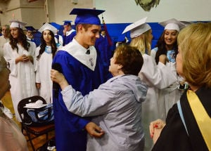 SACRED HEART GRADUATION: Graduate Theo Mercurio of Estell Manor is hugged by his Great-Aunt, Barbara Sciarretta of Vineland in the gym before graduation. Monday June 3 2013 Sacred Heart High School Graduation. (The Press of Atlantic City / Ben Fogletto)  - Photo by Ben Fogletto