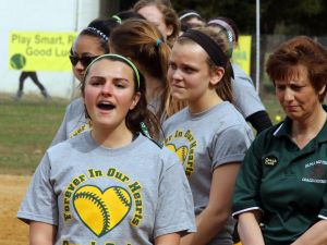 OLMA Softball: Our Lady of Marcy Academy Alyssa Rodriguez #23 sings the National anthem during the ceremony to honoring their former softball coach Jamie Cook who died suddenly over the winter at a young age Tuesday, April 8, 2014. - Edward Lea