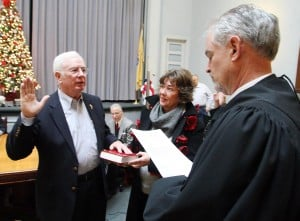 Cape Reorganization: Judge Louis J. Belasco, right, swears in William Murray as deputy mayor Tuesday at City Hall in Cape May. Murray was joined by his fiancee, Mary Scott.  - Photo by Edward Lea
