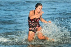 Tri-Resorts: Wildwood's Katie Collins runs to tag off after dismounting her board during the Paddle Board Relays. Monday July 15 2013 Tri-Resorts Lifeguard Championships in Strathmere. (The Press of Atlantic City / Ben Fogletto) - Photo by Ben Fogletto
